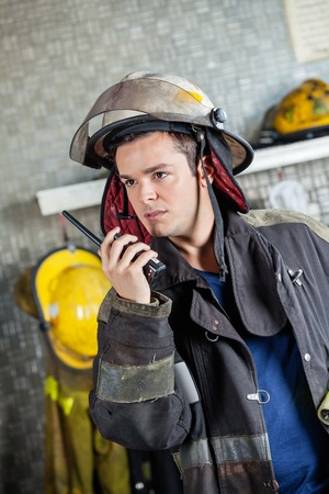 walkie talkie: Confident male firefighter looking away while using walkie talkie at fire station