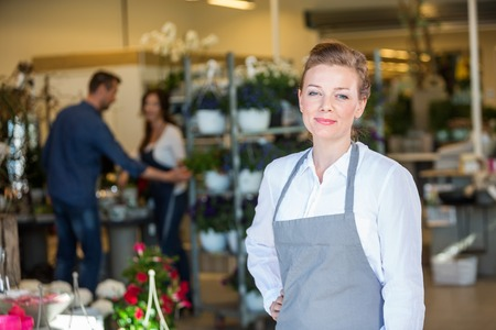 focus on foreground: Portrait of confident mid adult female salesperson at flower shop
