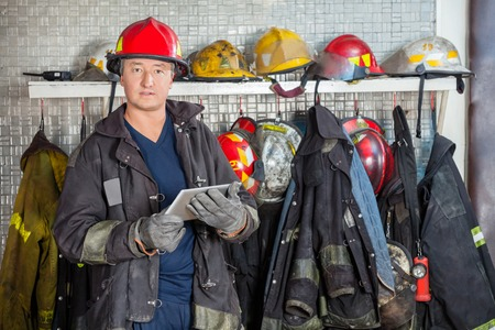 fireman: Portrait of mature fireman in uniform holding digital tablet at fire station