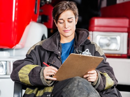 fire fighter: Young firewoman writing on clipboard while sitting against trucks at fire station Stock Photo