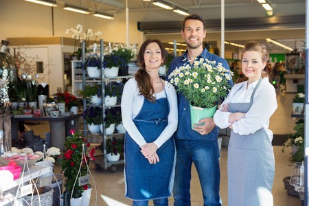 casual business man: Portrait of happy man holding potted plant white standing by salesgirls in flower shop Stock Photo
