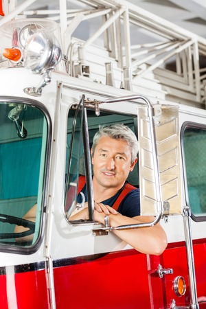 fireman: Portrait of confident mature fireman sitting in firetruck