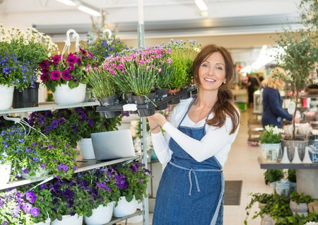 business service: Portrait of smiling mid adult botanist carrying crate full of flower plants in shop