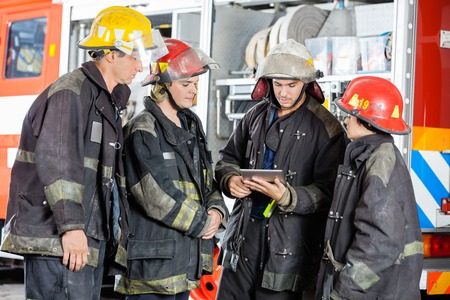 fire fighter: Young and mature firefighters using tablet computer against firetruck at station Stock Photo