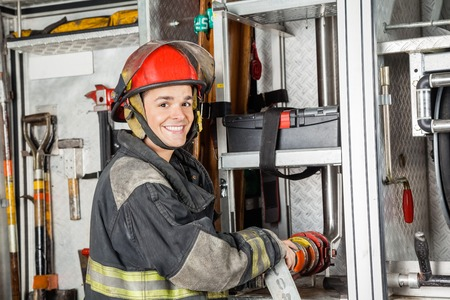 fireman: Portrait of happy male firefighter fixing water hose in truck at fire station Stock Photo