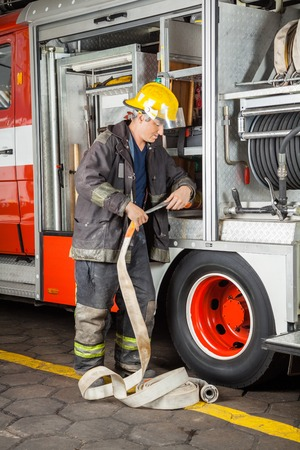 fire fighter: Mature male firefighter adjusting hose in truck at fire station
