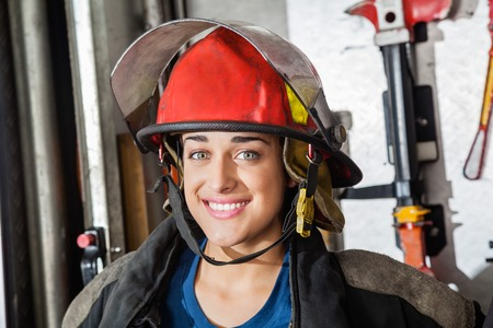firefighter: Closeup portrait of happy female firefighter at fire station