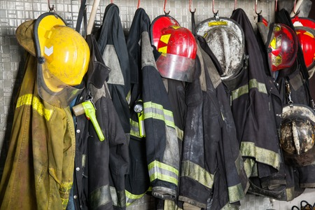 ropa de trabajo: Trajes de bombero y cascos que cuelgan en la estación de bomberos Foto de archivo