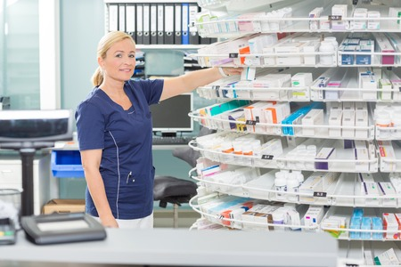 drugs: Portrait of confident female chemist arranging products in shelves at pharmacy
