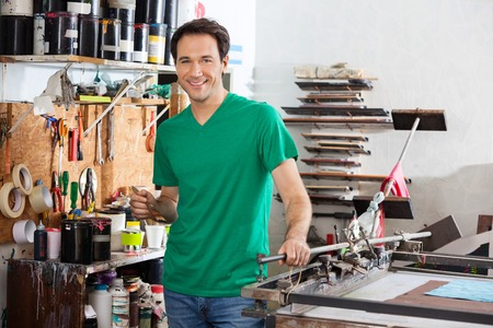 paper factory: Portrait of smiling man holding brush in paper factory Stock Photo