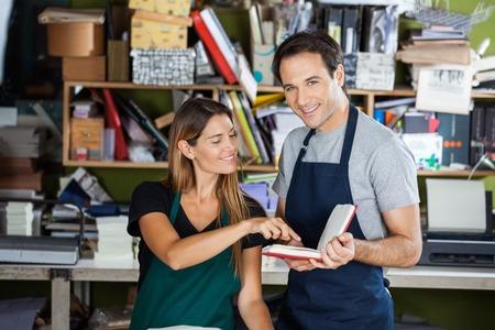 mujer trabajadora: Retrato de feliz libro de explotación trabajador de sexo masculino, mientras que su colega apuntando en la fábrica
