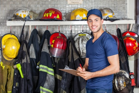 fire fighting equipment: Portrait of smiling worker holding clipboard while standing against uniforms hanging at fire station