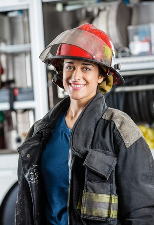 Portrait of happy female firefighter standing against firetruck at station