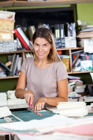 mid adult female: Portrait of mid adult female worker cutting paper in factory
