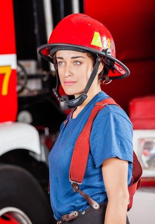 casco rojo: Firewoman Confiados en casco rojo mirando a otro lado mientras que se opone camión de bomberos