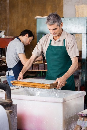 paper factory: Male worker dipping mold in pulp and water while coworker working at paper factory