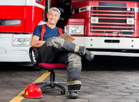 firefighter: Full length portrait of happy firefighter sitting on chair against trucks at fire station