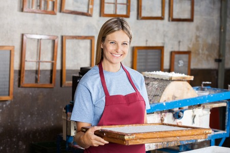 mid adult female: Portrait of confident mid adult female worker holding mold at paper factory