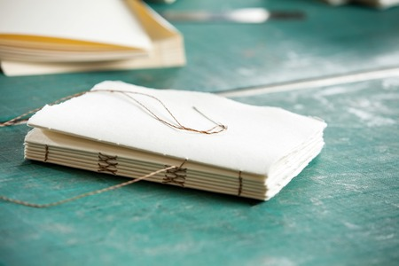 book binding: Closeup of thread and papers on table in factory