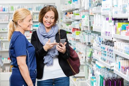 Smiling female customer showing mobile phone to pharmacist in pharmacy 版權商用圖片