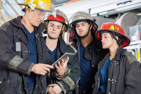 fire team: Team of firefighters using tablet computer at fire station Stock Photo