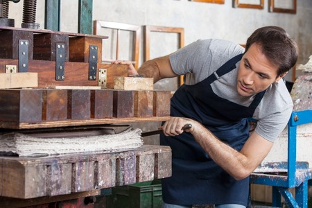 adult male: Mid adult male worker using paper press machine in factory Archivio Fotografico