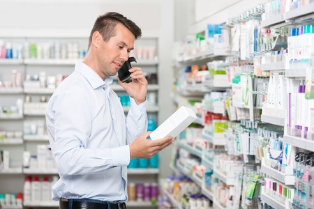 mid adult male: Mid adult male customer using mobile phone while holding product in pharmacy