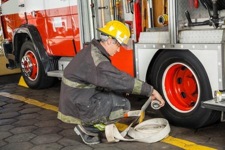 bombero: Bombero de sexo masculino que se agacha mientras sostiene la manguera por cami�n en el parque de bomberos