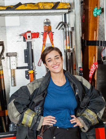 happy work: Portrait of happy female firefighter standing with hands on hips against firetruck at station