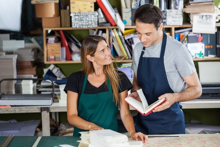 book binding: Mid adult female worker looking at colleague holding book in paper factory Stock Photo