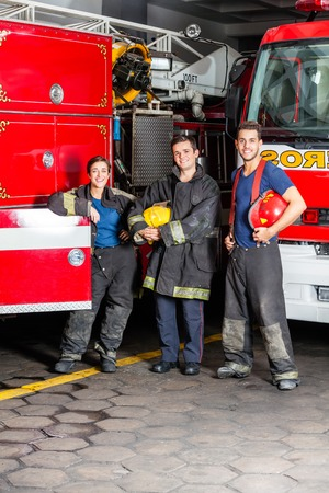leaning on the truck: Portrait of happy young firefighters standing against trucks at fire station