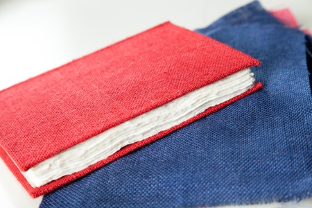 book binding: Closeup of fabric and red cover book on table in factory Stock Photo