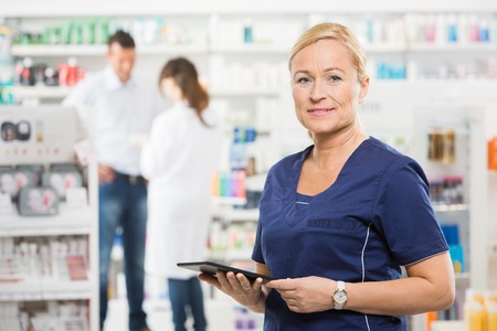 workers group: Portrait of confident assistant holding digital tablet while pharmacist and customer standing in background at pharmacy Stock Photo