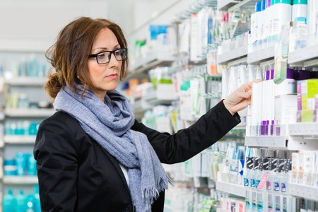 Mid adult female consumer choosing product in pharmacy