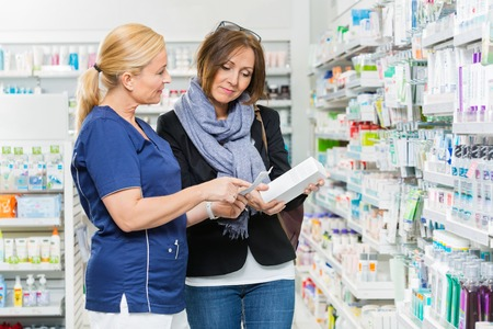 assistants: Mature chemist explaining product details to female customer in pharmacy