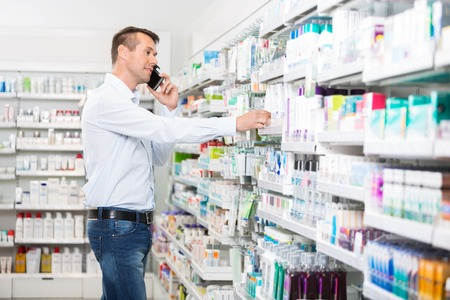 pharmaceutic: Mid adult man using mobile phone while selecting product in pharmacy