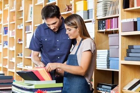 envelop: Mid adult female worker assisting male customer to choose envelop in shop