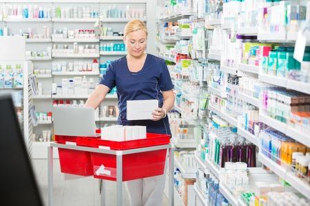 updating: Mature female pharmacist updating stock in laptop at pharmacy Stock Photo