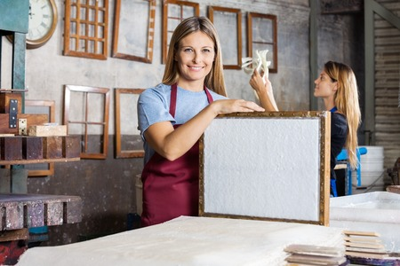 mid adult   female: Portrait of happy mid adult female worker holding mold with paper in factory