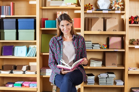 Portrait of smiling female customer holding book while sitting against shelves in shop