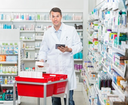 mid adult male: Portrait of mid adult male pharmacist counting stock while holding digital tablet at drugstore