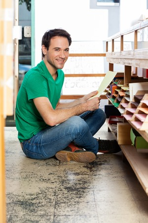 mid adult male: Full length portrait of mid adult male customer holding paper while sitting on floor in shop