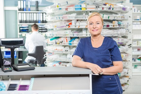 Portrait of smiling female pharmacist leaning at cash counter in pharmacy