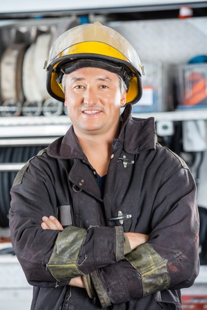 fireman: Portrait of happy mature fireman standing arms crossed at fire station