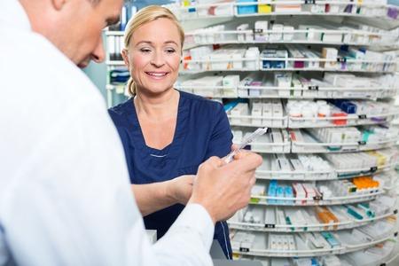 pharmacist: Smiling pharmacist explaining product details to customer in pharmacy Stock Photo