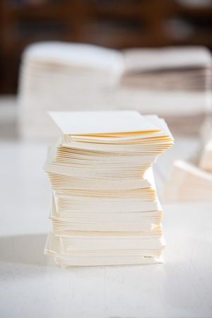empty table: Closeup of stacked white papers on table in factory