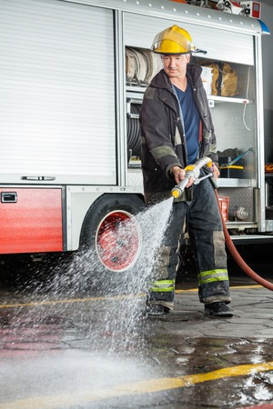 fireman with hose: Full length of mature fireman spraying water on floor during practice at fire station