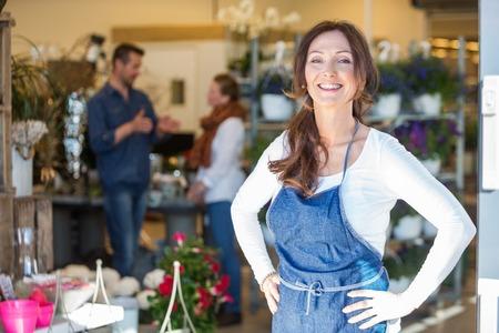 Portret van glimlachende vrouwelijke eigenaar met klanten in de achtergrond bij bloemenwinkel