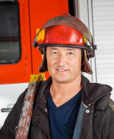 casco rojo: Retrato de bombero masculina confía en casco rojo de pie contra el camión de bomberos en la estación Foto de archivo