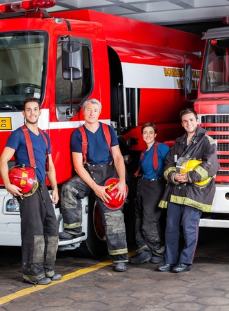 leaning on the truck: Portrait of confident firefighters leaning on trucks at fire station Stock Photo